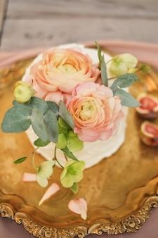 Arranjo de bolo rosa decorado com flores de ranúnculo