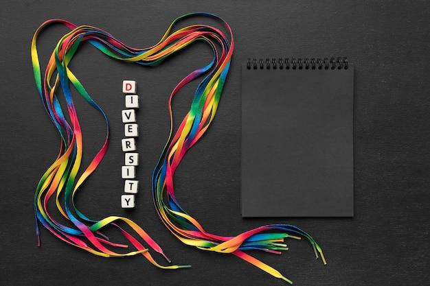 Arranjo de cadarços coloridos em fundo escuro com bloco de notas preto