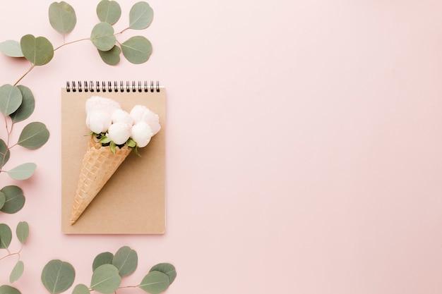 Arranjo de casquinha de sorvete floral e notebook