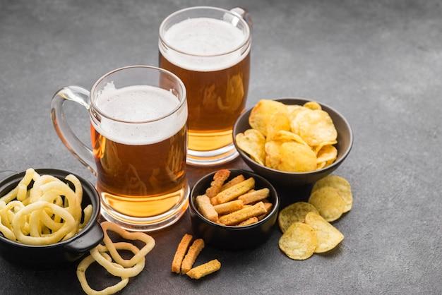 Arranjo de chips e canecas de cerveja