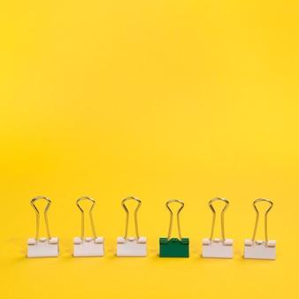 Arranjo de clipes de papel com um clipe de papel verde