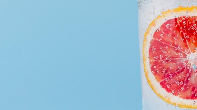 Arranjo de close-up com fatia de laranja vermelha em um copo