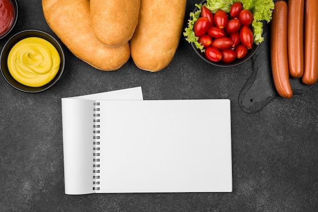 Arranjo de comida plano com caderno