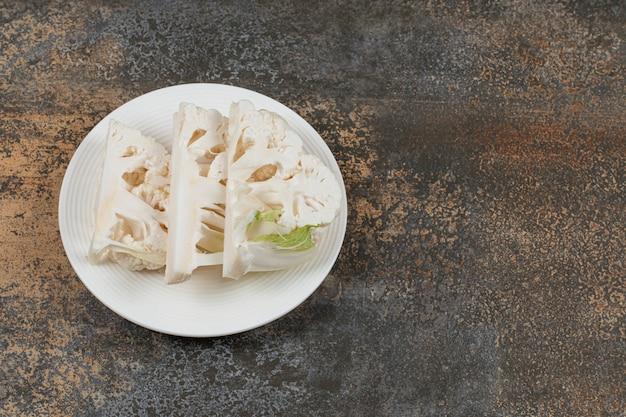 Arranjo de couve-flor fatiada no prato, na superfície de mármore