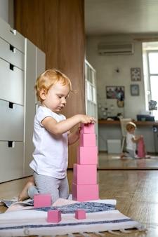 Arranjo de crianças alegres em cubos rosa montando materiais educacionais para maria montessori na torre