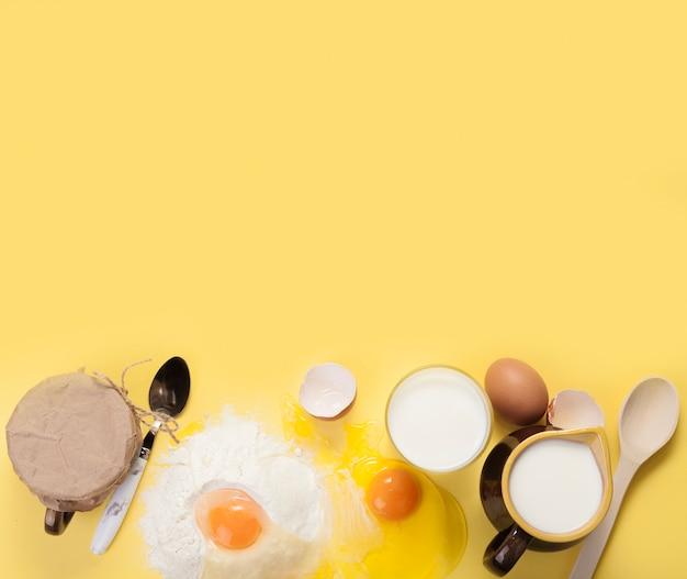 Arranjo de diferentes ingredientes em fundo amarelo, com espaço de cópia