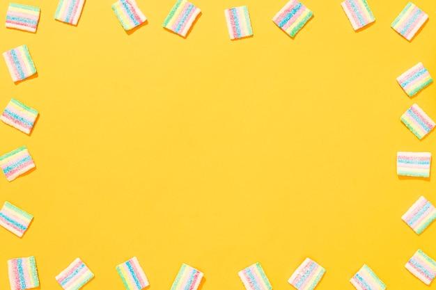 Arranjo de doces coloridos diferentes em fundo amarelo, com espaço de cópia