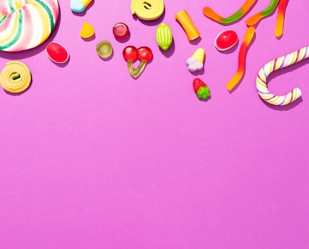 Arranjo de doces coloridos diferentes em fundo rosa com espaço de cópia