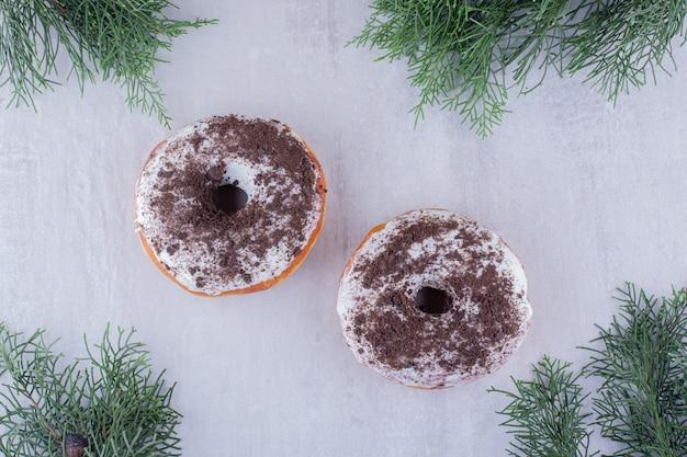 Arranjo de donuts entre folhas de cipreste em fundo branco.
