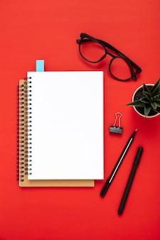 Arranjo de elementos da mesa com o caderno vazio em fundo vermelho