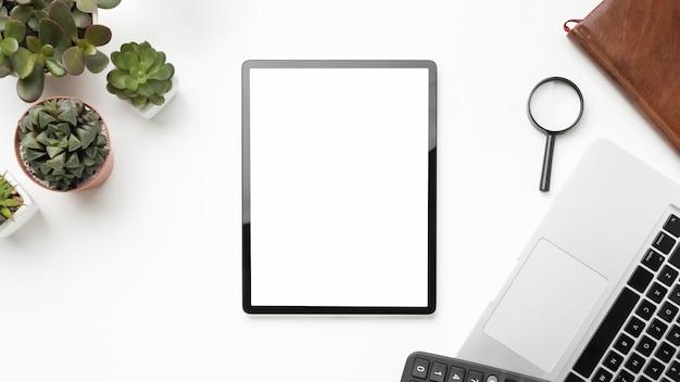 Arranjo de elementos de mesa plana com tablet de tela vazia