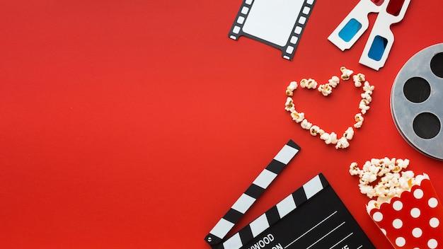 Arranjo de elementos do cinema em fundo vermelho, com espaço de cópia