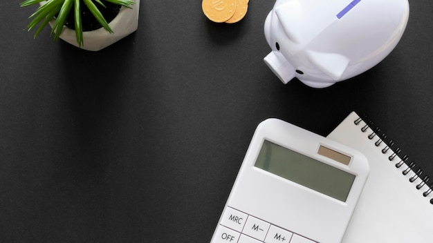 Arranjo de elementos financeiros com bloco de notas vazio e calculadora