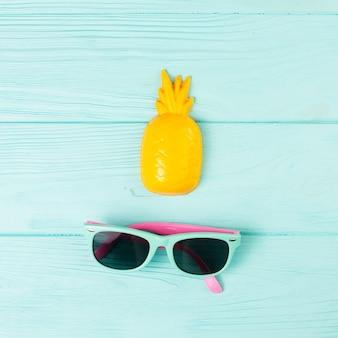 Arranjo de férias tropical com óculos de sol e abacaxi