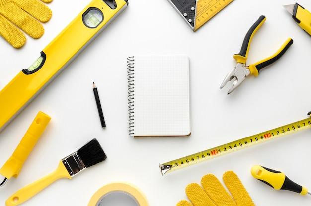Arranjo de ferramentas de reparo e bloco de notas amarelos