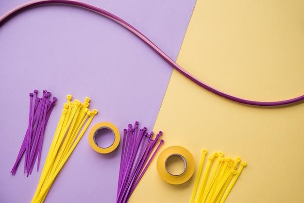 Arranjo de fita isolante e nylon zip fio sobre pano de fundo duplo roxo e amarelo