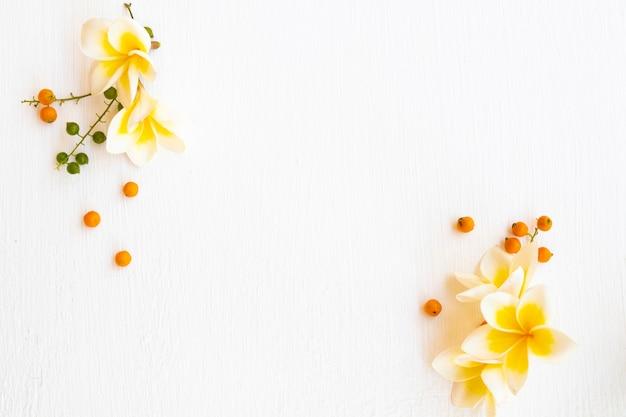 Arranjo de flores amarelas frangipani plana lay estilo cartão postal