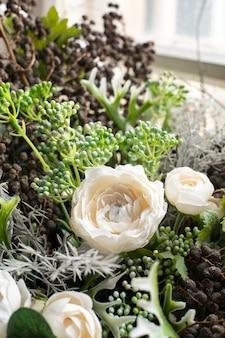 Arranjo de flores brancas e flores secas em uma cesta de vime