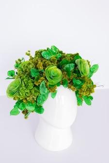 Arranjo de flores com flores verdes secas e vaso em forma de cabeça