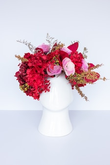 Arranjo de flores com flores vermelhas secas e vaso em forma de cabeça