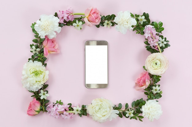 Arranjo de flores com um telefone móvel em uma moldura floral, vista superior e plana leigos