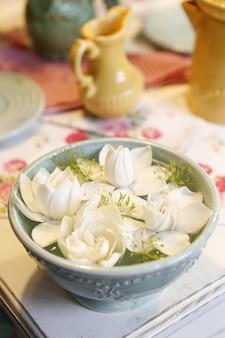 Arranjo de flores de jasmim em uma panela com água