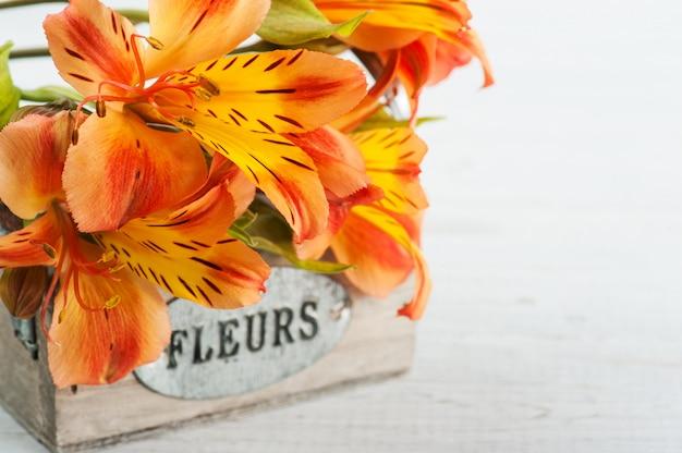 Arranjo de flores de lírio laranja em caixa de madeira