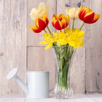 Arranjo de flores de tulipa em um vaso de vidro com saudação de coração, decoração de regador na parede de fundo de mesa de madeira, close-up, conceito de design do dia das mães.