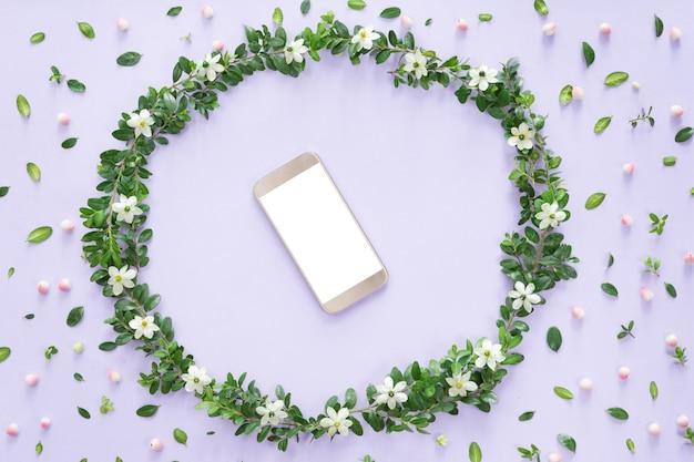 Arranjo de flores ou composição com um telefone móvel em um quadro floral, vista de cima, plana leigos