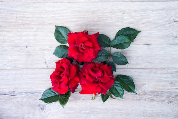 Arranjo de flores rosas vermelhas isolado em fundo cinza de madeira