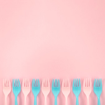 Arranjo de garfos de plástico colorido em fundo rosa
