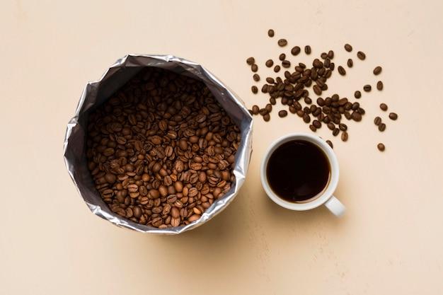 Arranjo de grãos de café preto sobre fundo bege com uma xícara de café