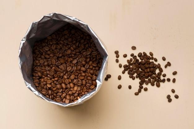 Arranjo de grãos de café preto sobre fundo bege
