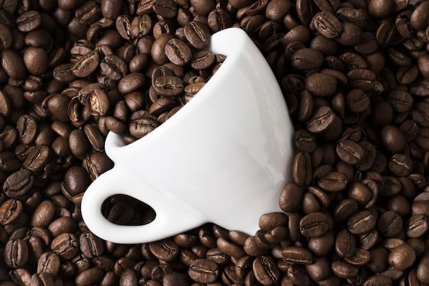 Arranjo de grãos de café torrados e xícara branca