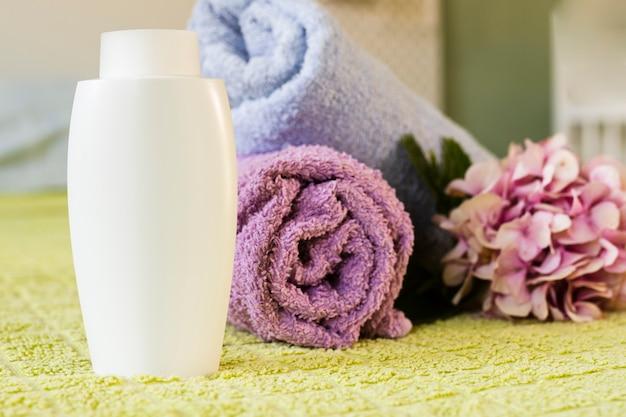 Arranjo de itens de banho com toalhas e mamadeira