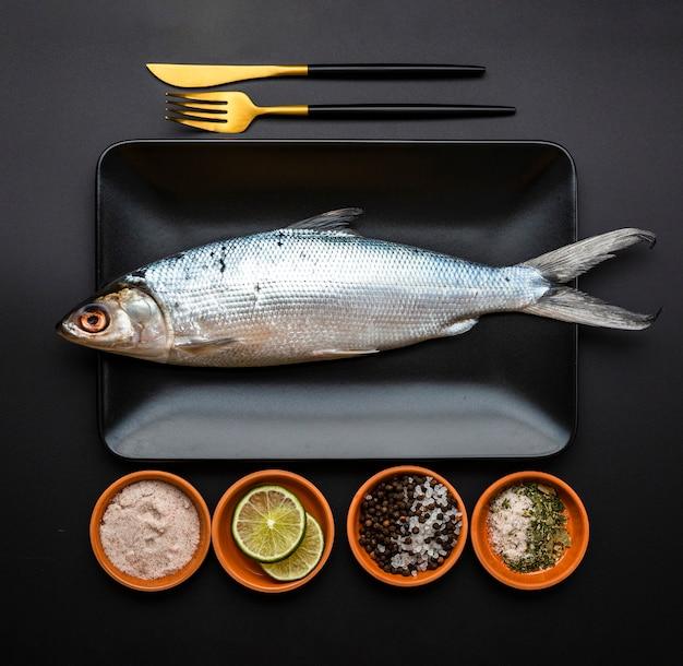 Arranjo de latão plano com peixe na bandeja