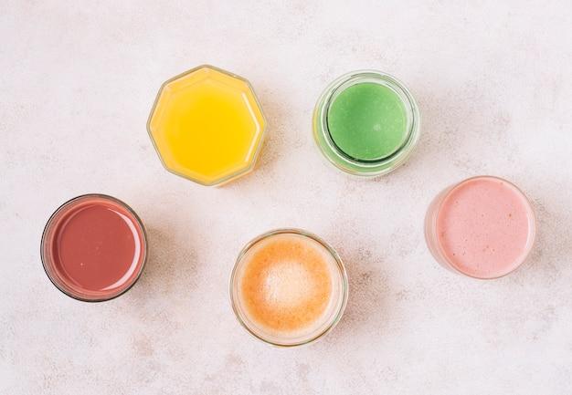 Arranjo de leigos planos de smoothies coloridos