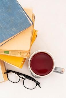 Arranjo de livros com copos e xícara