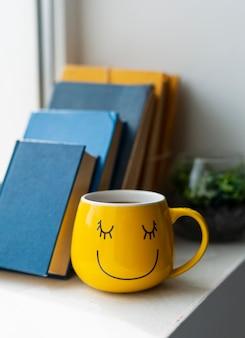 Arranjo de livros e copo amarelo
