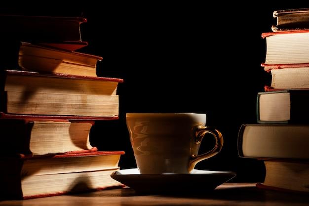 Arranjo de livros e copo