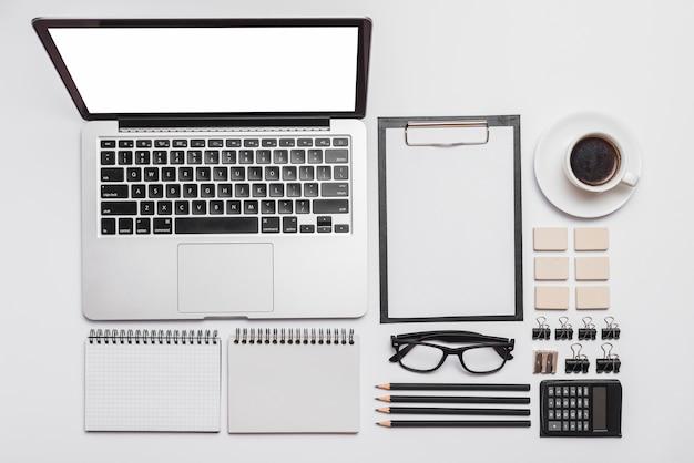 Arranjo de mesa de escritório com laptop; suprimentos e xícara de café