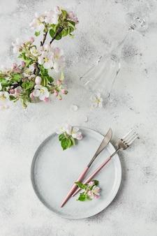 Arranjo de mesa de primavera com galhos de macieiras em flor e flores na mesa