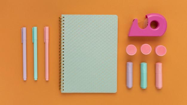 Arranjo de mesa plana com caderno e canetas