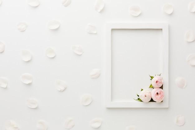 Arranjo de moldura vazia branca com rosas e pétalas