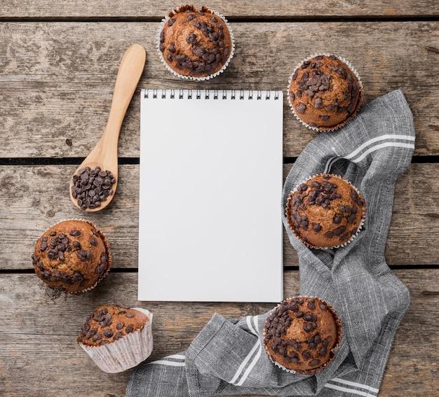 Arranjo de muffins assados e bloco de notas vazio