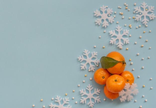 Arranjo de natal com tangerinas laranja e flocos de neve brancos