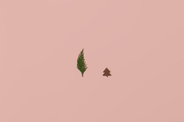 Arranjo de natal moderno feito com árvore de natal de madeira, enfeite de coração vermelho e galho de árvore perene em fundo rosa claro brilhante. conceito mínimo de natal com espaço de cópia.