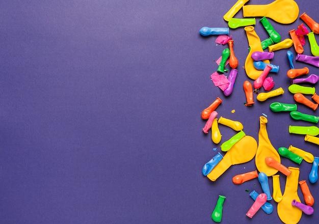 Arranjo de objetos festivos coloridos sobre fundo azul, com espaço de cópia
