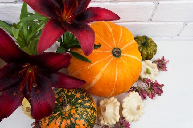 Arranjo de outono com flores de lírio vermelho e abóboras