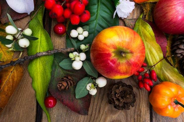 Arranjo de outono com maçã, flores de seda branca de abóbora de areia, vista superior